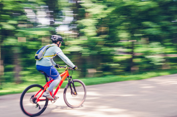 A cyclist in a helmet rides a bicycle path, motion blur