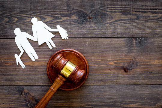 Family law, family right concept. Child-custody concept. Family with children cutout near court gavel on dark wooden background top view copy space