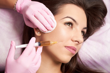 Close-up of beautiful woman getting injection in the cosmetology salon. Doctor in medical gloves with syringe injects cheeks drug.