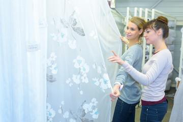 Women looking at sheer curtain