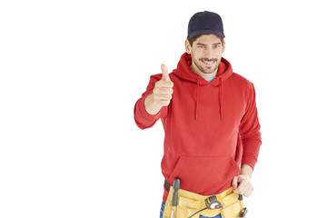 Young repairman with tool belt giving thumb up standing against white background