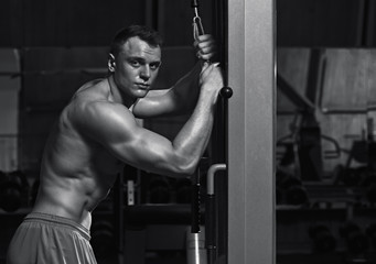 Fit strong athletic man using sport equipment in the gym, black and white image
