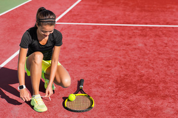 Sport fitness woman getting ready to play tennis on red clay court tying up shoe laces. Exercise summer training fit girl motivation. Racket and tennis ball on background.