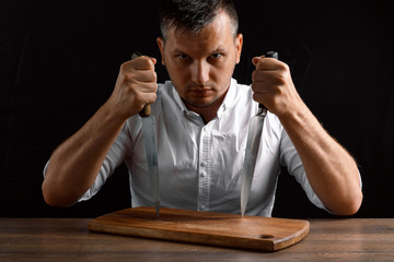 Hands of the chef close-up with a knife and a wooden board on a dark background. The concept of cooking, cooking, recipe dishes.