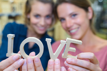 Women holding wooden letters to spell love