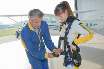 Instructor fastening harness onto parachutist