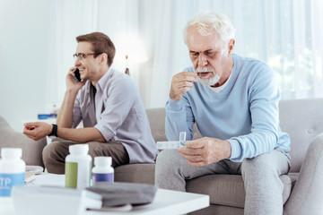My own business. Gay male caregiver using phone while senior man placing pill in mouth
