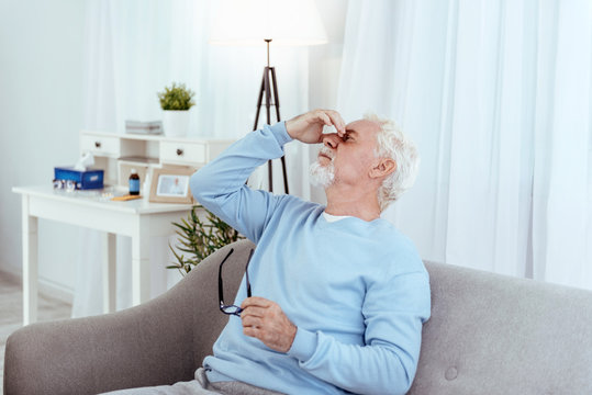 Low blood pressure. Tired senior man touching nose bridge and holding glasses