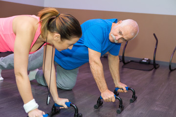 senior man exercising on resistancewith personal trainer in gym