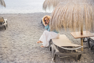 nice smiled curly blonde hair lady on vacation sitting on a beach setas under umbrella tropical style use modern smartphone to stay connected with friends at home. outdoor modern activity