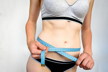 Slim young girl measuring her waist with blue tape measure on gray background. Slim and fitness concept.