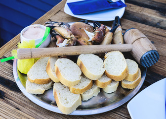 plate with boiled legs and claws of brown crab with bread and dip on rustic wooden table