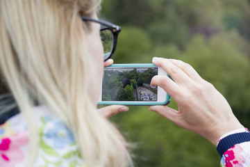 A girl holding a phone to photograph a landscape view.