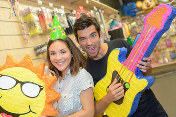 Couple in joke shop with fun props