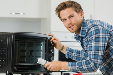 man cleaning up after replacing the filter in a microwave