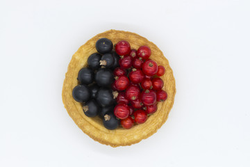 Tartlet with red and black currant isolated white background