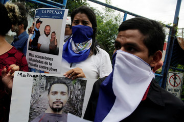Relatives and friends hold pictures of their loved ones during a protest to demand the release of demonstrators detained during anti-government protests outside a prison in Managua