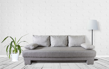 Modern couch with cusions, standard lamp, yucca plant in flower pot near white bricks wall. Interior decor mock up.