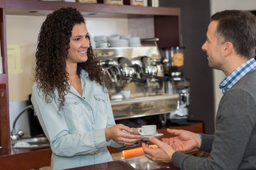 young female barista serving coffee to customer in cafe