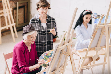 Portrait of elegant senior woman painting sitting at easel in art studio with smiling female teacher giving comments, copy space