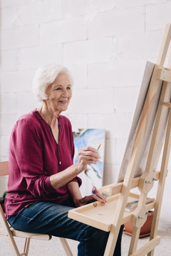 Portrait of modern senior woman painting picture sitting at easel in art studio and enjoying work in class