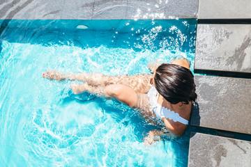 Woman sits in swimming pool
