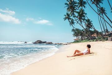 Woman takes sunbath on tropical beach. Island paradise