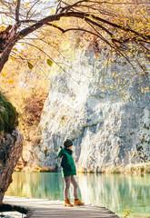 Weekend walk in autumn park: boy stay on wooden bridge near the mountain lake