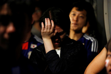 Japanese fans react after Japan losing match as they watch a broadcast of the World Cup Round of 16 soccer match Belgium vs Japan at a sports bar in Tokyo