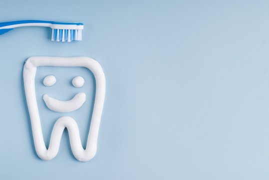 Toothbrush and tooth paste on a blue background
