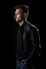 man on a black background / young man on a black background in a leather jacket