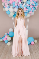 Portrait of a beautiful young girl with curly blonde hair. Standing in a long light dress against the background of white and blue balloons