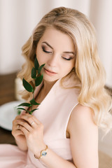 Portrait of a beautiful young girl with curly blonde hair in a delicate dress on a light background. Eyes look down with beautiful makeup closeup