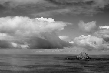 A black and white version of Storm Island beneath a bank of cumulus clouds