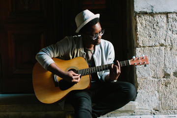 African musician playing guitar in the city