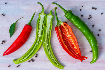 different kinds of pepper on a white wooden table