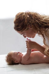 Young woman mother kissing her newborn baby girl at home
