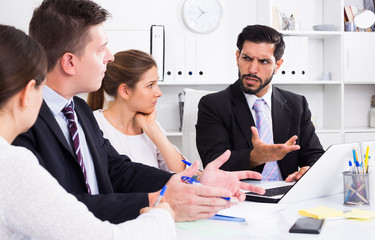 Outraged manager with colleagues at meeting