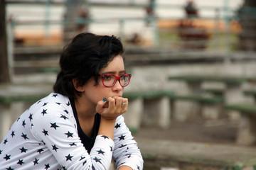 retrato de  menina jovem  sentada com expressao  pensativa