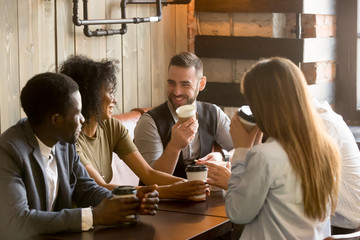Smiling multiracial people enjoying coffee, talking spending pleasant time together in cozy coffee shop, diverse friends drinking from paper cups, meeting at work break for casual conversation in cafe