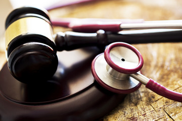 Medical law concept. Gavel and stethoscope on wooden table
