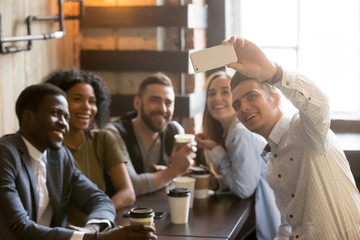 Millennial multiracial friends smiling posing for camera, taking self-portrait on smartphone while enjoying coffee in cafe, young people making selfie on mobile phone at meeting in coffee shop.