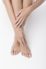 Wall Murals Pedicure Beautiful legs and hands on white background. Pedicure and manicure time.