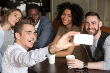 Diverse colleagues taking group photo on smartphone spending time together in coffeeshop, smiling multiracial millennial friends making self-portrait, sitting at coffee table having fun in cozy cafe