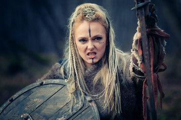 Mad furious viking woman warrior in the attack. Sward and shield. Close-up portrait. Book Cover