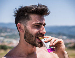 Young muscular shirtless man eating protein bar outdooron a balcony in summer