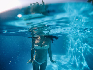 Pregnant woman under the water of a pool