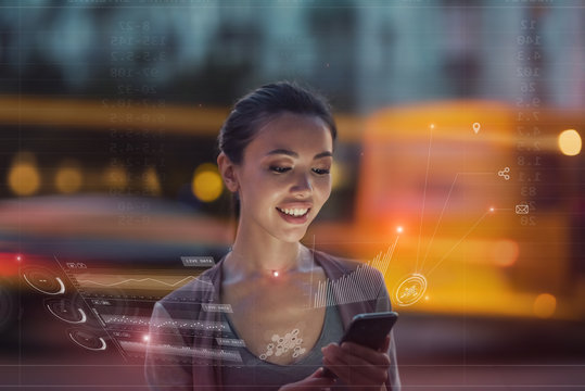 Staying up to date with technology in a fast moving world, concept. A young asian woman is using an innovative future technology to view her phone data and functions in holographic display around her