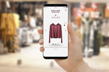 Online shopping with smartphone, clothing store in background