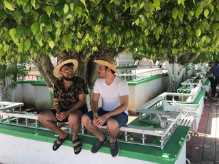 Graphic designer Carlos Alfredo Ramos (L) and artist Isaac Cabrera Leon chat while sitting in the shade of a park in Tepetitan